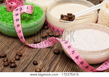 Anti cellulite cosmetic products. Sea salt, natural body scrub, cellulite cream containing caffeine with coffee beans and body measuring tape. Shallow depth of field