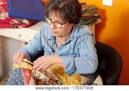 seamstress woman sewing for finish a quilt