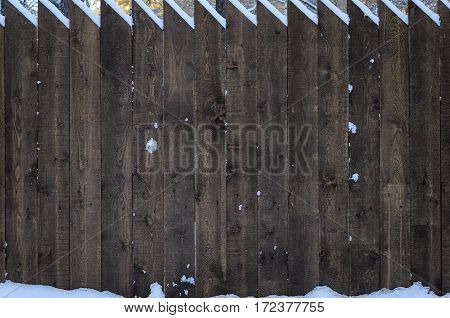 The fence of acute pine logs, close-up, snow, yellow leaves, snow, winter