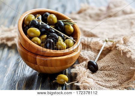 Wooden Bowl Of Green And Black Olives.