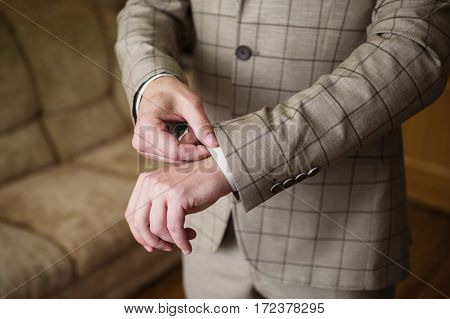 A man correct sleeves on the shirt. Men's style. Professions. To prepare for work
