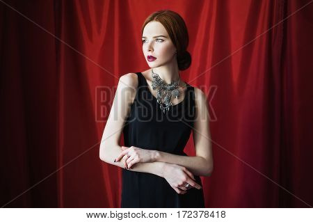 Beautiful red-haired girl in black dress with necklace around her neck on red background looking away. Fashion photography. Bright appearance. Red hair. Woman posing hands
