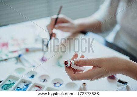 girl painter in white dress draws paints