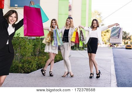 Beautiful girls with shopping bags in ctiy near mall. Shopping and tourism concept