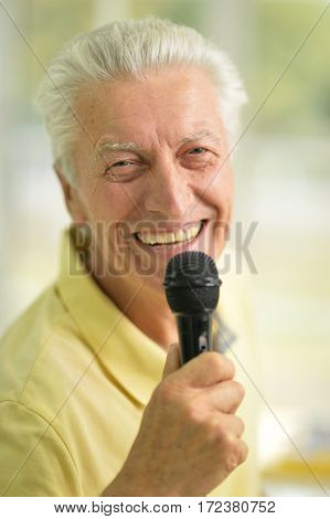 Portrait of a excited senior man holding microphone