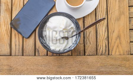 Closeup of icecream coffee cup and smart phone on table