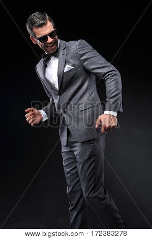 young businessman posing with gray suit on black background