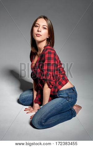 Casual girl wearing jeans and red checked shirt sitting barefooted at floor smiling at camera, studio shot