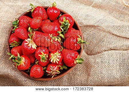 strawberry in a clay plate on a sacking tablecloth