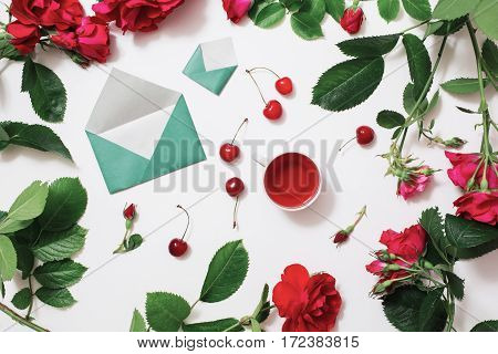 Red Rose tea ripe cherries small envelopes with green leaves roses lay on a white background. Tea drinking during work. Healing drink. Send mail. Berry compote. Flower frame. Flat lay top view art