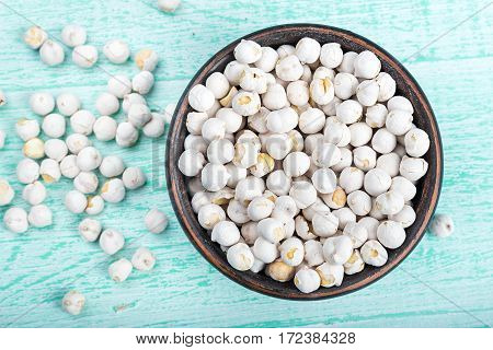 Chickpeas in a bowl on a wooden background top view
