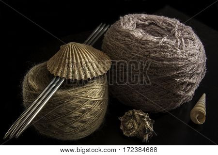 Two balls of wool needles and seashells on a black background. yarn of isolated