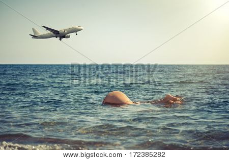 Young girl dives into the sea against the backdrop of the aircraft. Women's buttocks in seawater