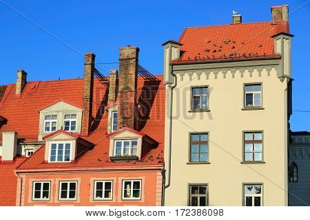 Old residential house on Livu square with pigeons on the tiled roof. Old Riga, Latvia