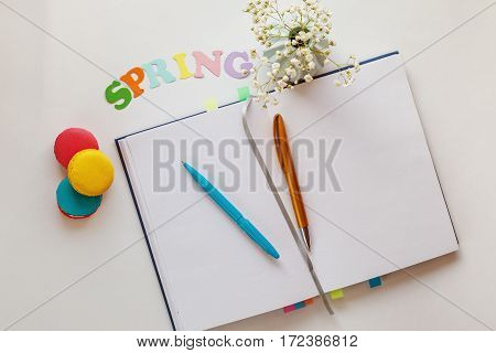 Top view image of spring word open blank notebook and colourful macaroons