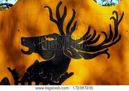 Antlered animal painted on a piece of wood.