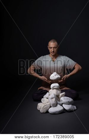 Handsome man sitting on the floor in yoga pose meditating with his eyes shut pile of white stones lying near studio shot