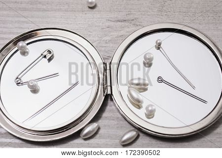Double mirror pins needles and sewing items white beads on a light wooden background work of seamstresses