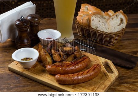 Hot Sausages Serving On Wooden Board With Beer