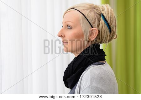 Young woman looks thoughtfully out the window - portrait with copy space