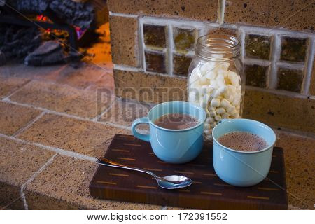 Two mugs of delicious hot chocolate by a fireplace.