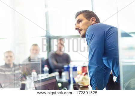 Businessman making a presentation at office. Business executive delivering a presentation to his colleagues during meeting or in-house business training, explaining business plans to his employees.
