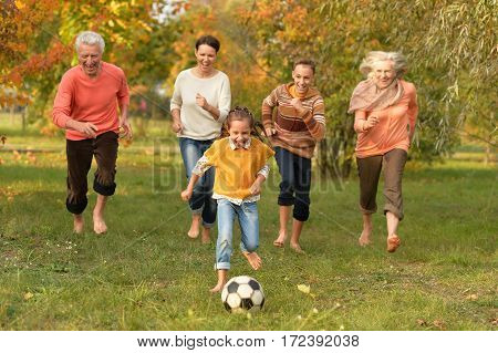 Portrait of a family playing football outdoors in autumn