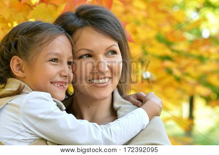 young mother and daughter in autumn park
