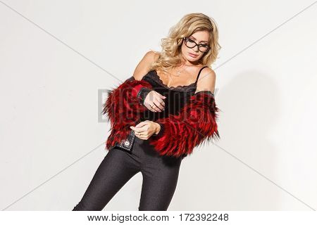 Beautiful business girl sexy blonde elegant trousers and fur coat posing on white background