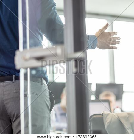 Businessman making a presentation at office. Business executive delivering a presentation to his colleagues during meeting or business training. View through glass. Business and entrepreneurship.