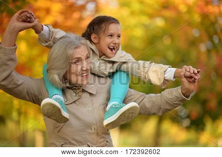 portrait of happy grandmother and granddaughter posing outdoors in autumn