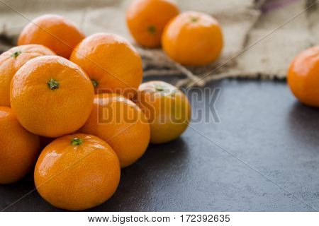 A pile of mandarin oranges on a stone slab.