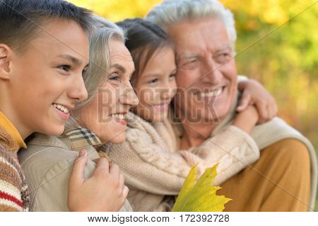 portrait of grandparents with grandchildren posing outdoors in autumn