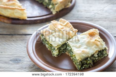 Spanakopita - Greek spinach pie on the wooden background