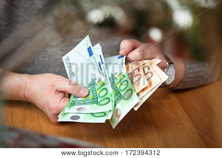 male hands think Euro banknotes. Euro banknotes in denomination of 100 and 50 Euro. Wealthy businessma. Calculate the profit