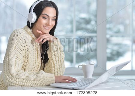 Portrait of a young woman in headphones using laptop