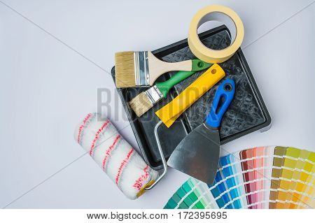 color swatches rollers and brushes on a black tray
