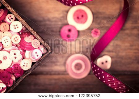 A close up of a box of pink and white buttons, with a pink polka dot ribbon alongside. Filtered to have a faded nostalgic look.