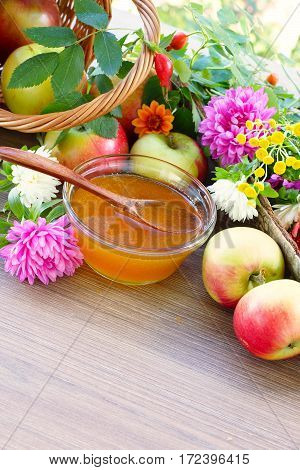 Apples crumbled from the basket. Floral honey and garden flowers. Free space for text
