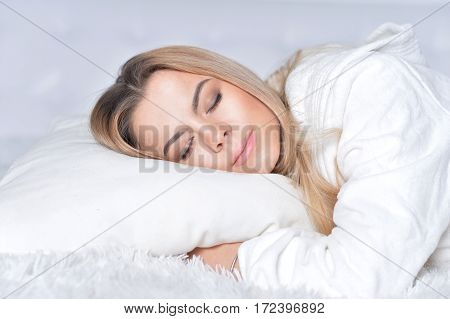 Portrait of a beautiful blonde girl sleeping in a bed