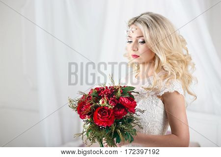 Gorgeous blonde bride with curly hairstyle in vintage white lace wedding dress holding red peonies bouquet, sensual look.