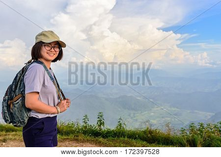 Teens girl hiker wear a cap and glasses with backpack is standing and smiling happily on high mountain at scenic point of Phu Chi Fa Forest Park in Chiang Rai Province Thailand