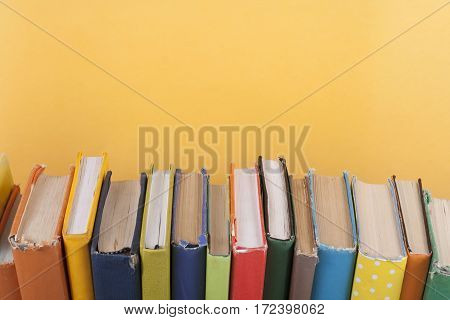 Book stacking. Open hardback books on wooden table and yellow background. Back to school. Copy space for ad text.