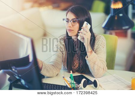 Woman sitting in home office at desk working on computer and talking on mobile phone.