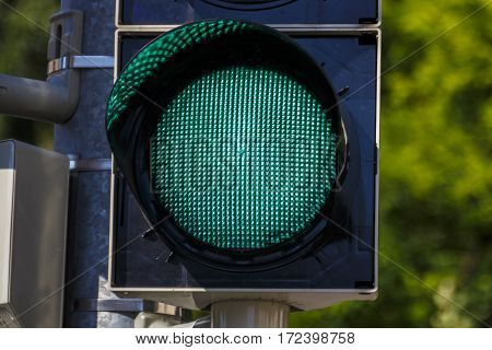 Closeup of a traffic light on green in Munich with a tree in the background