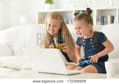 Portrait of a cute little sisters play video game