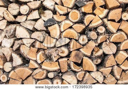 background of oak firewood stacked in a flat wall, close-up