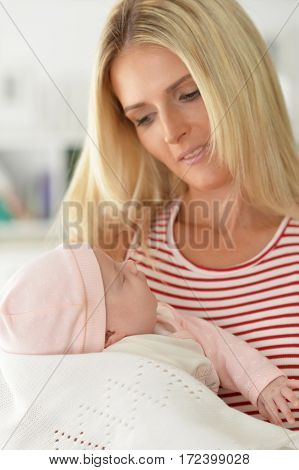 young woman with sleeping baby at home
