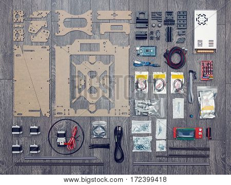 Flat lay of electronic and mechanical parts and components of DIY 3d printer on wooden surface