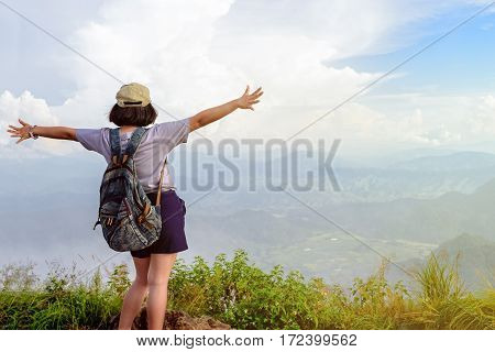 Happy teens girl hiker with backpack and cap open arms looking beautiful nature landscape on high mountain at viewpoint of Phu Chi Fa Forest Park during sunset in Chiang Rai Province Thailand